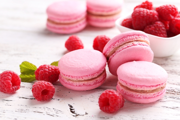 Raspberry macarons on white wooden background